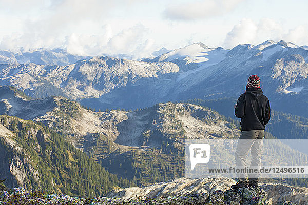 A hiker looks out a a beautfiul mountain view from a rocky ridge in Pinecone Burke Provincial Park  British Columbia  Canada.