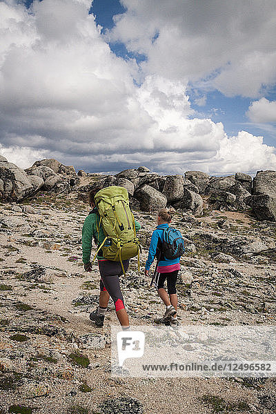 A mother and her young daughter backpacking in Cathedral Lakes Provincial Park  British Columbia  Canada.