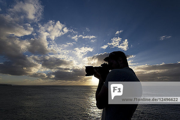 Photographer in action. Silhouette of a photographer at sunset with the ocean in the background
