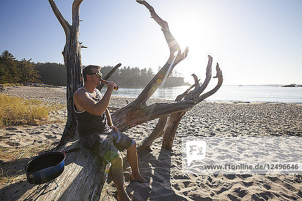 A Man Sitting On Log Drinking Beer On The Beach