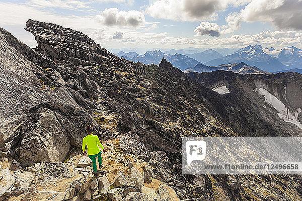 Young Woman Hiking Along A Rocky Ridge After Climbing Mount Marriott