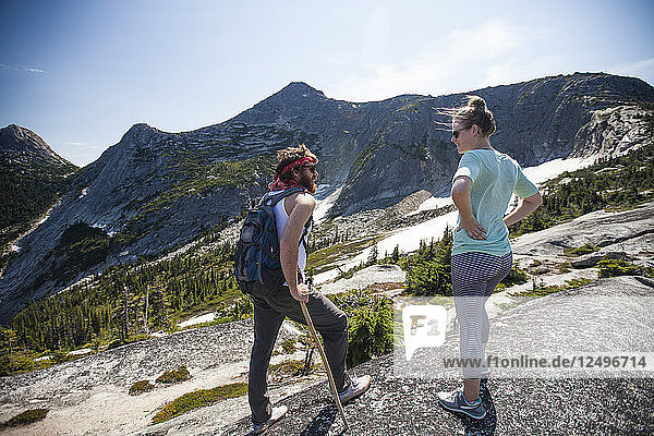 Two backpackers stop to converse while hiking toward Needle Peak  British Columbia  Canada.