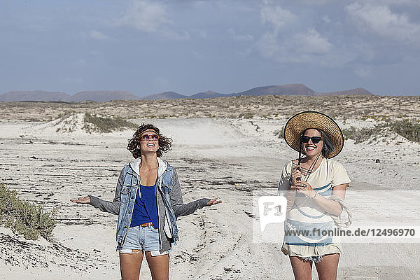 Two girls having fun in the middle of the desert  Fuerteventura Canary Islands