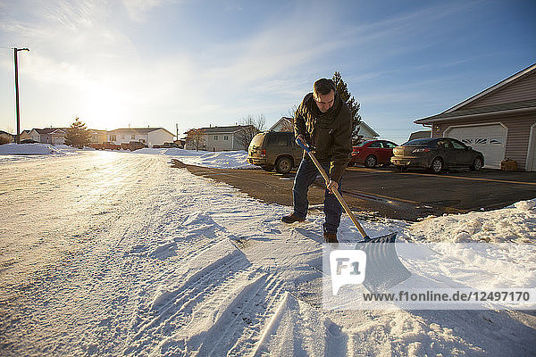 A man scrapes snow off his driveway in northern Alberta.