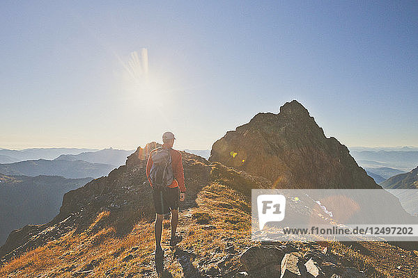 A Backpacker Approaches The Summit Of Tomyhoi Peak