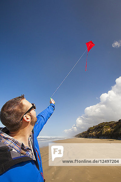 A young man looks up at his red kite in the sky while visiting a beach along the Oregon Coast