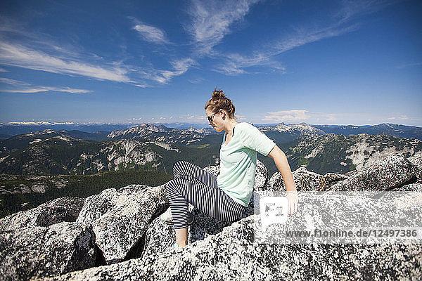 A young woman downclimbes granite rock on the summit ridge of Needle Peak  British Columbia  Canada.