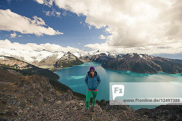 A female hiker stands on the summit of Panorama Ridge  with Garibaldi Lake in the background in Garibaldi Provincial Park  British Columbia  Canada.