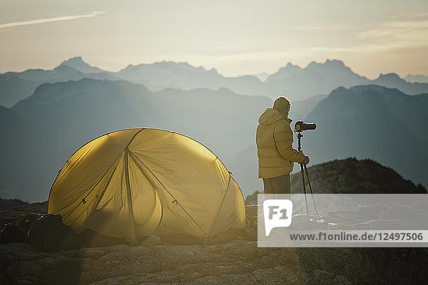 A photographer captures an image using a tripod early in the morning while camping on a rocky mountain ridge in southwest British Columbia  Canada.