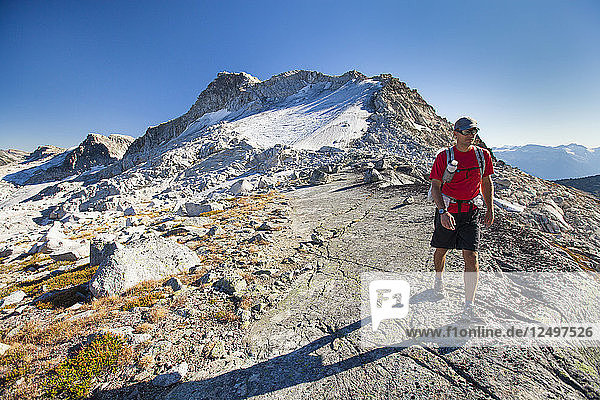 A backpacker hikes from Cassiope Peak towards Saxifrage Peak during a traverse trip near Pemberton  British Columbia  Canada.