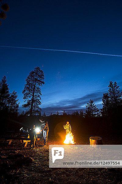 Todd Davis  Eugenia Clahan  and Hakkan Davis Sitting Around a Fire at Night While Camping at Gold Lake Campground in California