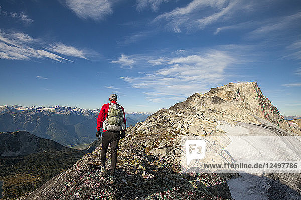 A backpacker hikes a rocky ridge near Saxifrage Mountain  Pemberton  British Columbia  Canada.