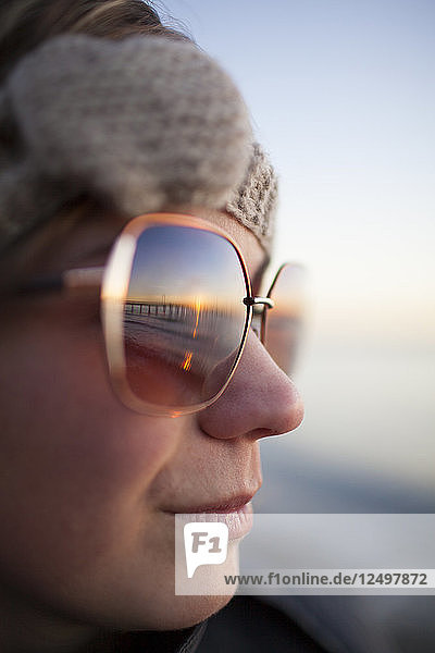 Portrait of a young woman wearing sunglasses at sunset  BC  Canada.