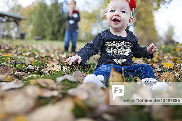 A Smiling Baby Playing With Leaves At Park