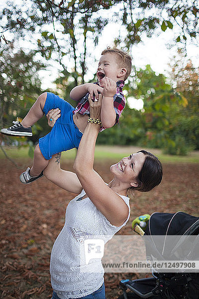 Mother Lifts Her Baby Into The Air Playfully At The Park