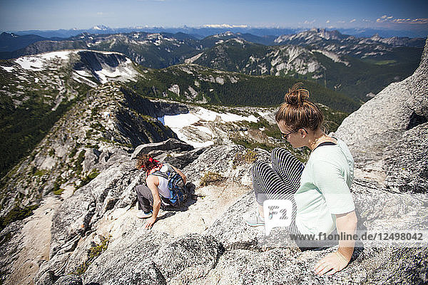 A young couple scramble down granite rock on the summit ridge of Needle Peak  British Columbia  Canada.