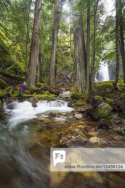 A photographer takes a picture of Cedar Hollow Falls in North Cascades National Park  Washington.
