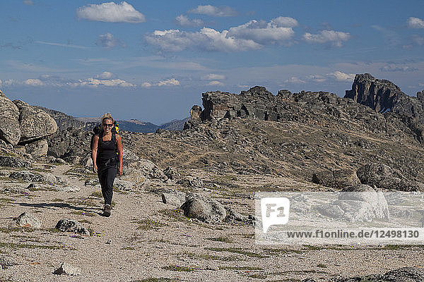A fit woman hiking through Stone City in Cathedral Lakes Provincial Park  British Columbia  Canada.