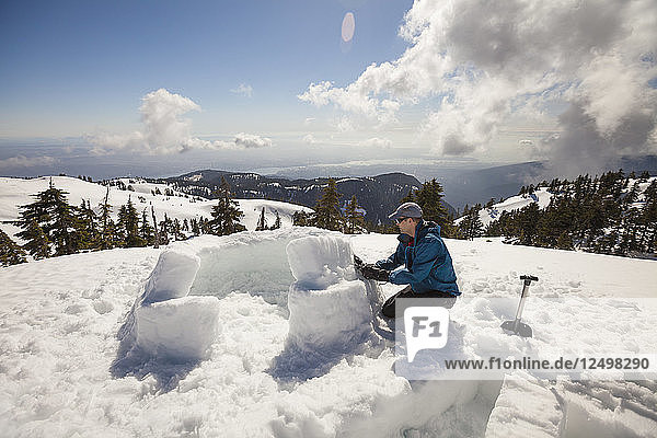 A Man Uses Snow To Fill The Cracks On The First Two Rows Of A Block Igloo On Seymour Mountain  Canada