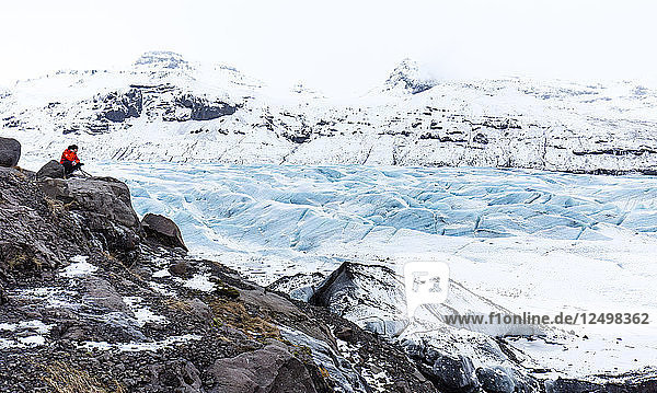 Sole Observer Looking Out Over The Crevasses Of A Glacier In The Icelandic Landscape