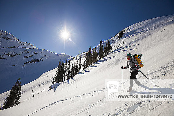 A fit female backpacker descends a snow covered mountain shortly after sunrise.