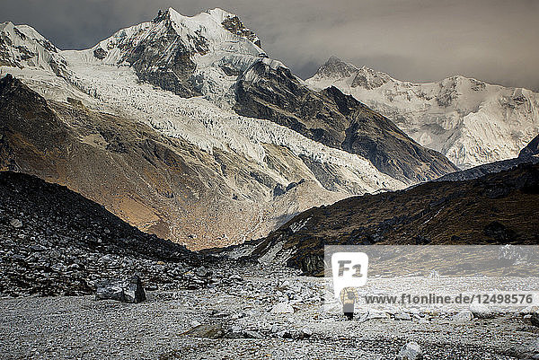 2 hikers walk towards the pass at Goeche-La with Kanchenjunga  the world's 3rd tallest mountain looming in the background