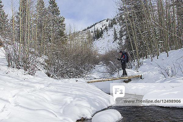 Crossing a small bridge over a frozen creek.