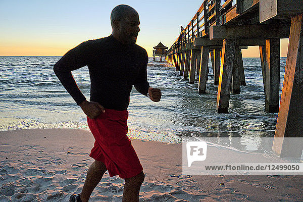 Man running on the beach at sunset with a pier in the background