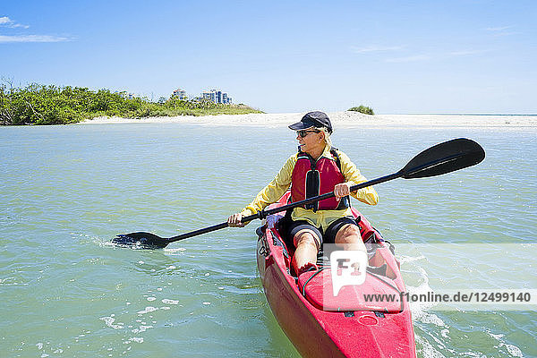 Woman paddling a kayak with the beach behind