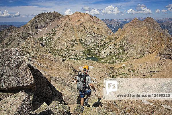 Man Descending From The Summit Of Windom Peak