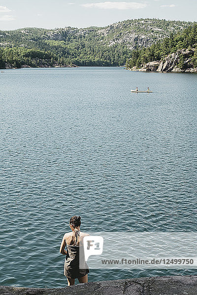 Young Woman Wrapped In Towel While A Canoe Is Crossing The Lake