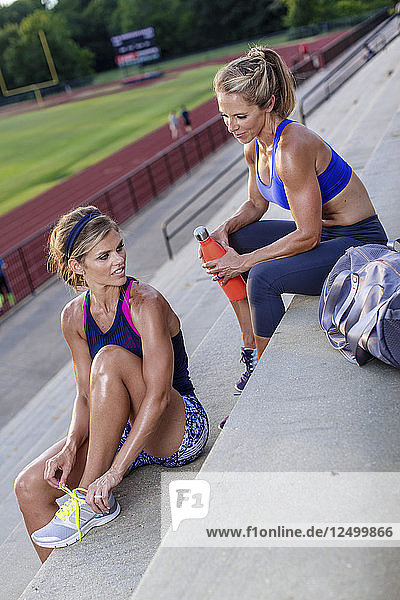Two Athlete Women Relaxing On Staircase