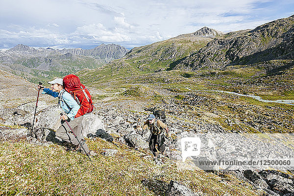 Man And Woman Hiking Up A Steep Hill In Talkeetna Range In Alaska  Usa