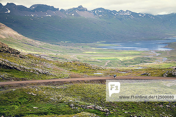 Distant View Of A Woman Rides Along A Mountain Road In North Iceland