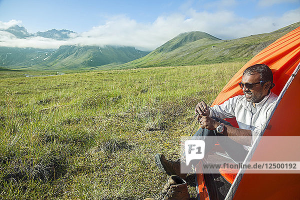 A Man Prepares To Leave His Tent At Camp In Lake Clark National Park And Preserve  Alaska  Usa