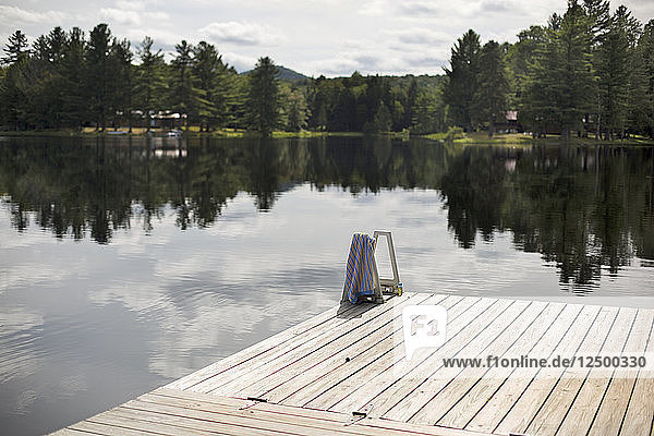 Dock Over Adirondacks Lake With Reflection Of Trees In It