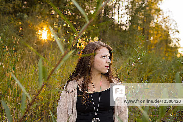 Female high school senior poses for a portrait outdoors at Armitage Park in Eugene Oregon. Senior portraits are a popular photo session that celebrates a young adult's entry into adulthood.