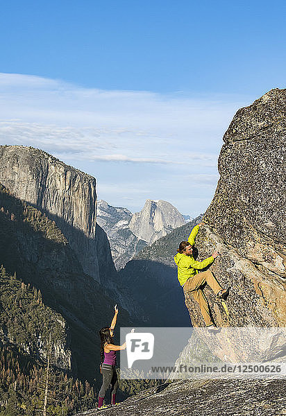 Climbers Bouldering On Rock In Yosemite With Half Dome And El Capitan In Background