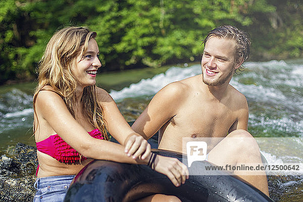 A young man and woman smile while resting on rock waterfall after tubing down a river.