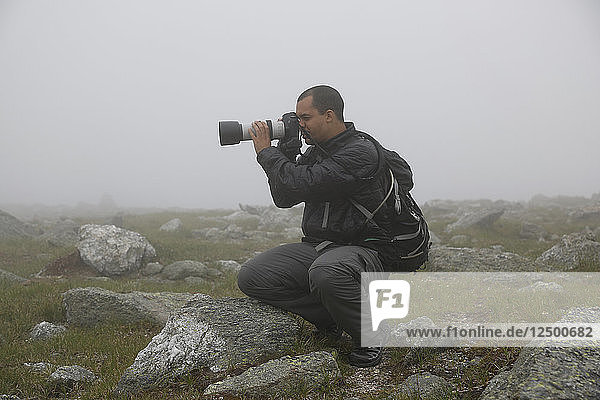 Male Photographer Taking Picture Of Mount Washington During Heavy Cloud Coverage