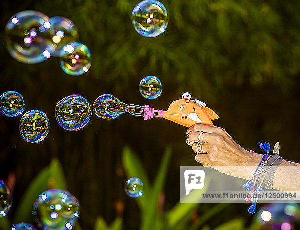 Young Asian womans blowing bubbles.