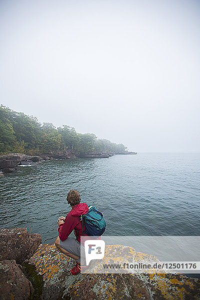 Male Hiker On Top Of Rock Exploring Lake Superior In Wisconsin