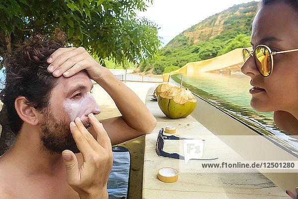 Man in swimming pool putting on sunscreen