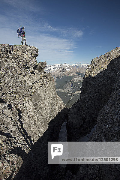 Hiker Standing On Top Of Rock Exploring Rocky Mountain In Alberta  Canada