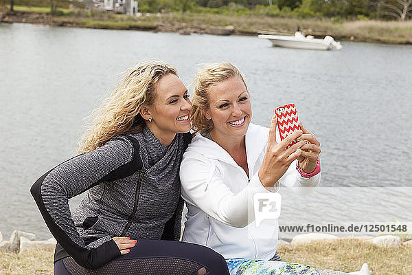 Two female friends taking selfies at the beach near the water wearing hoodies.