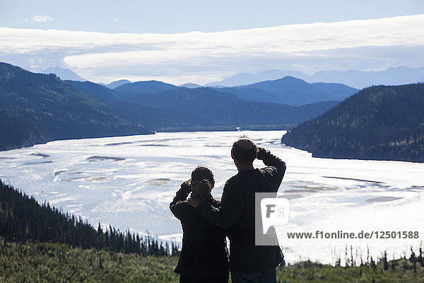 A man and woman look out over the Chitina River river valley near Chitina  Alaska.