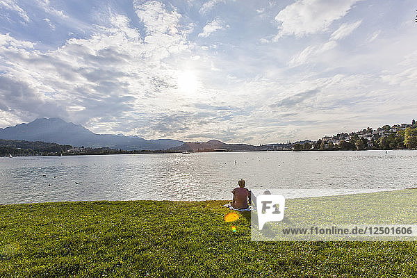 A couple sitting on in the grass on the shores of Lake Lucerne in Switzerland overlooking the nearby Rigi and Pilatus mountains and the Alps.