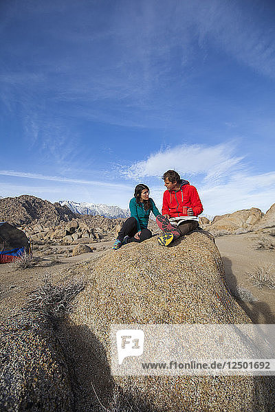 A man and woman sharing a journaling moment on a boulder in the Alabama Hills near Lone Pine California.