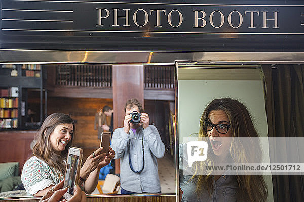 Group Of People Taking Picture Of Each Other In A Photo Booth