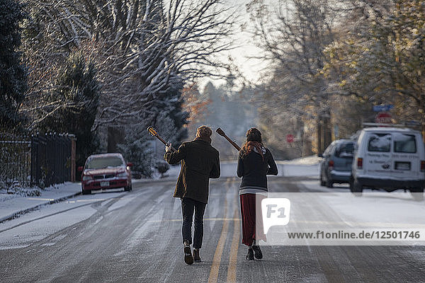 Musicians Ian Van Ornum (left) and Dani Aubert walk down a street in Boulder  Colorado playing their mandolin and banjo.